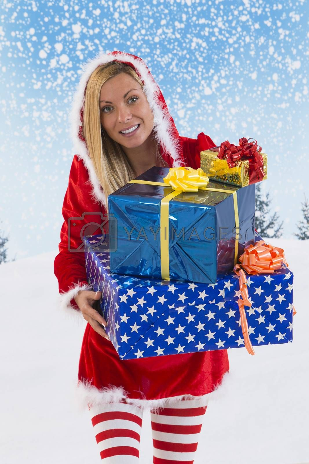 Beautiful young woman in Santa Claus clothes  with gifts on blue sky background