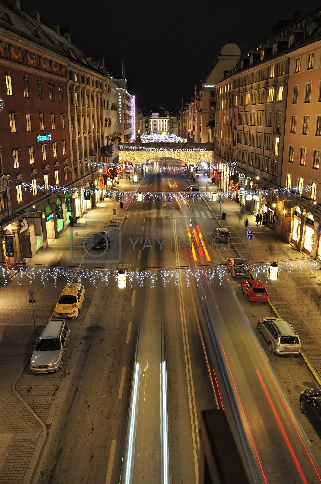 Night traffic on Kungsgatan in central Stockholm. Cars, pedestrians, taxis in traffic close to the crossing with Sveavagen