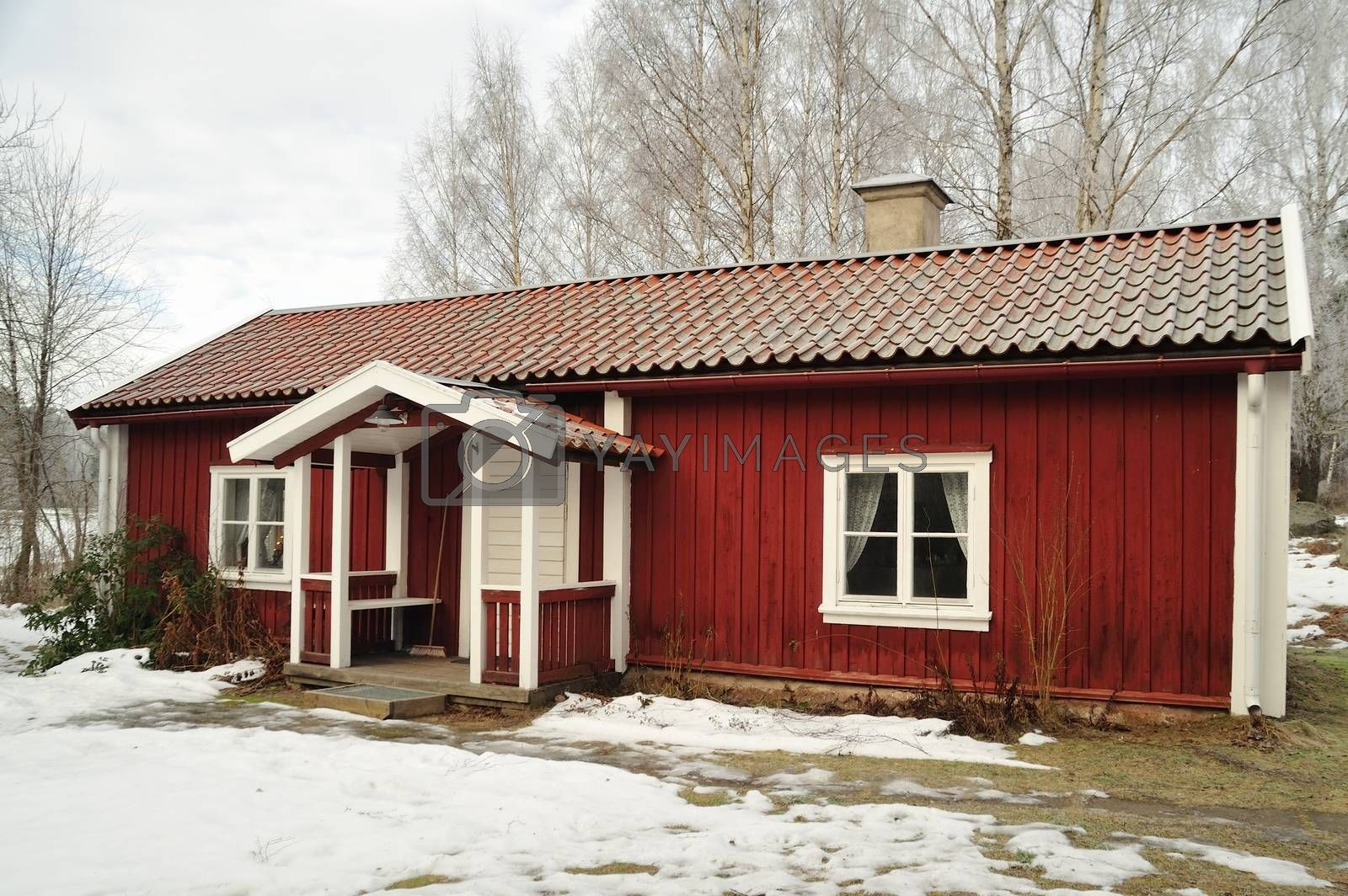 Typical red wooden house in Sweden on a clear and cold winter day