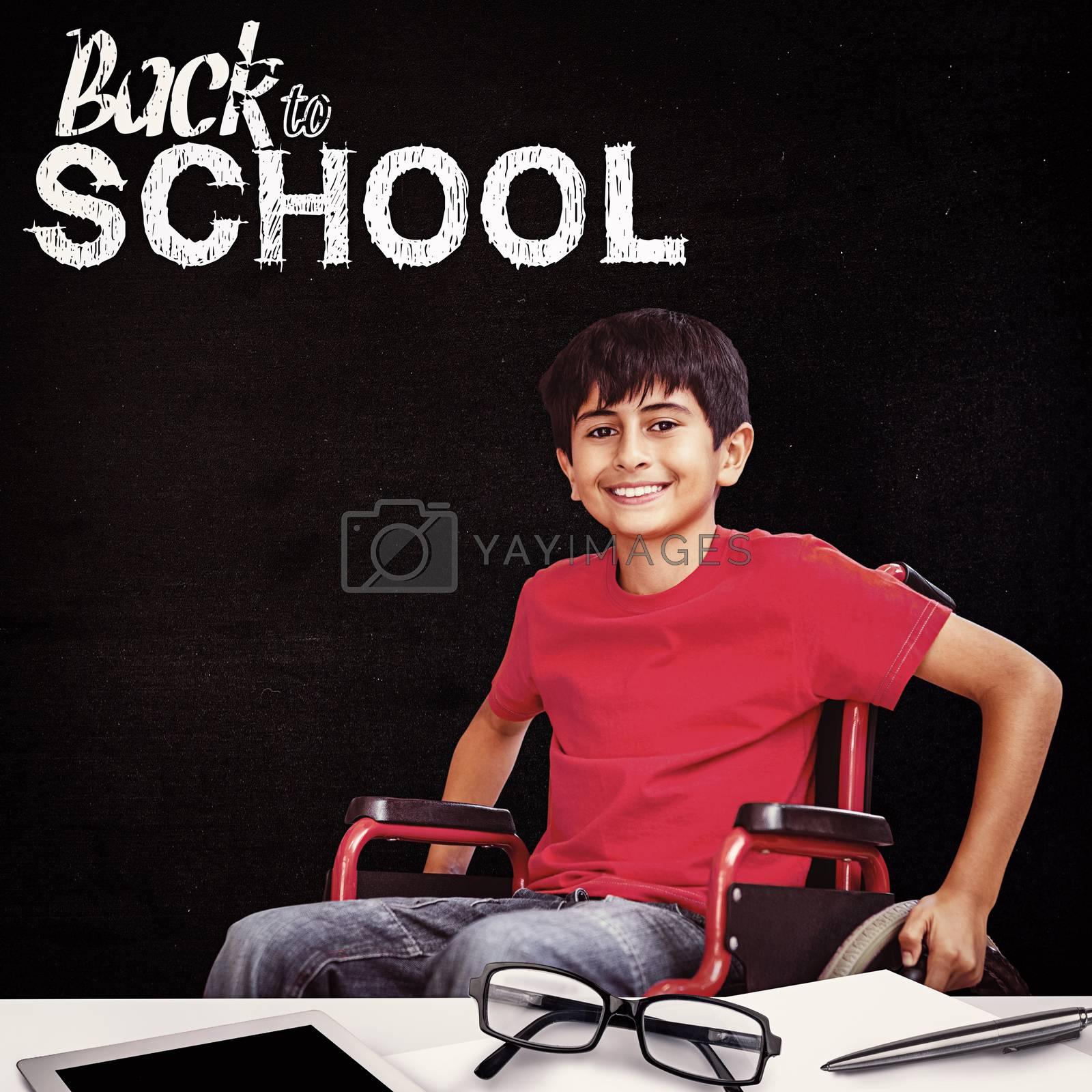 Portrait of boy sitting in wheelchair against black