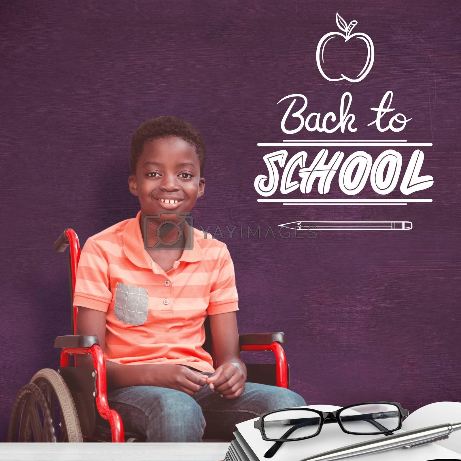Full length portrait of happy boy on wheelchair against green chalkboard