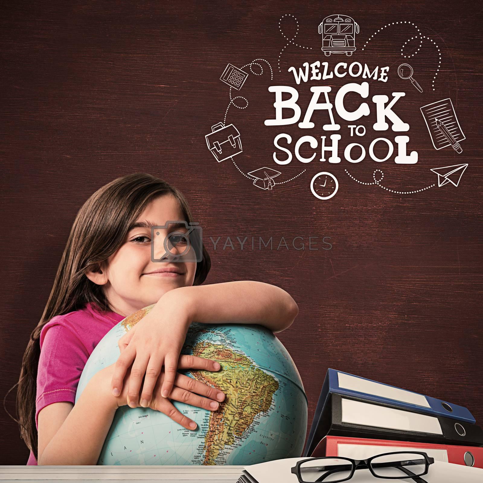 Cute pupil smiling holding globe against desk