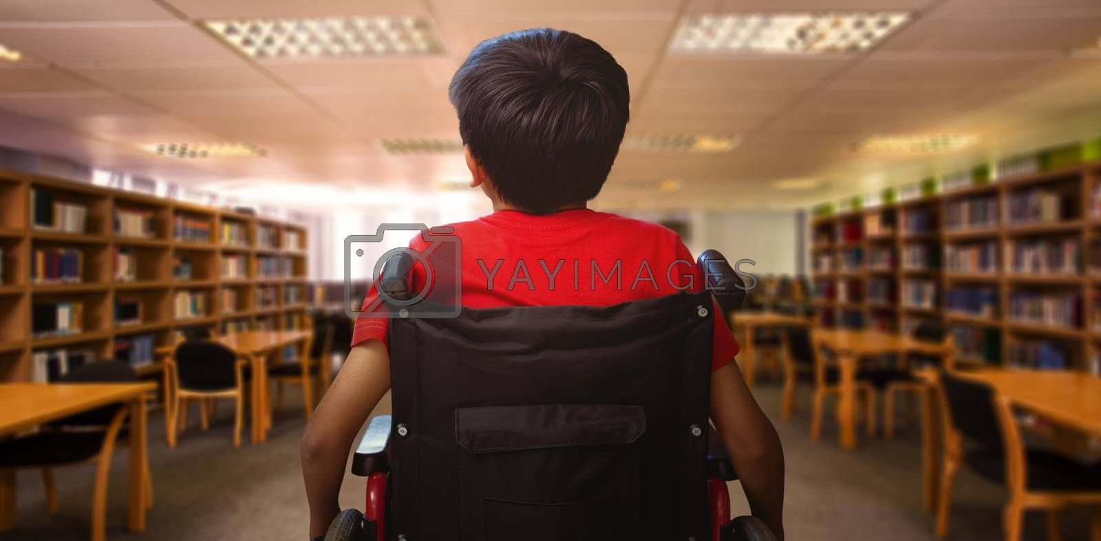 Rear view of boy sitting in wheelchair against view of library