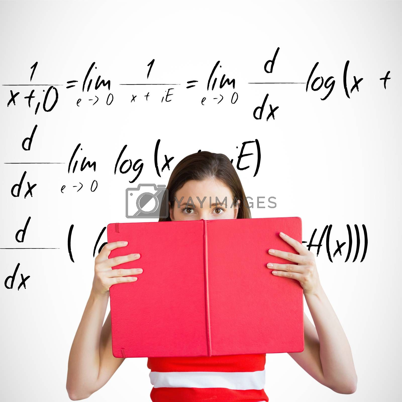 Student holding book over face against maths equation