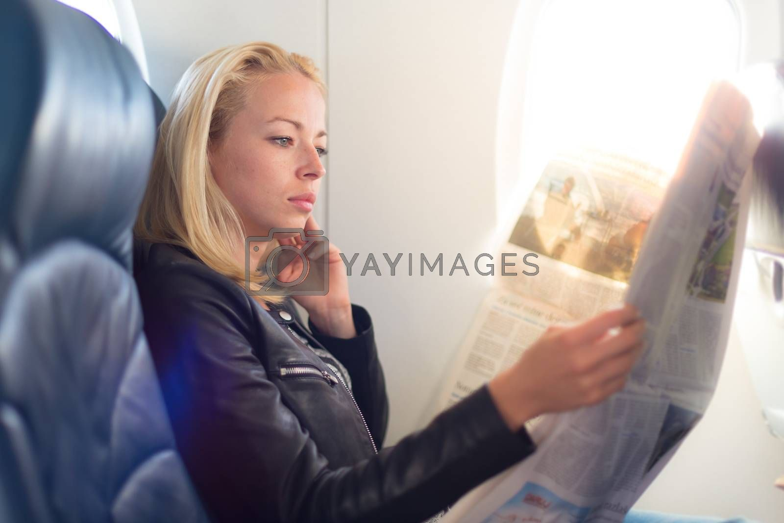 Royalty free image of Woman reading newspaper on airplane. by kasto