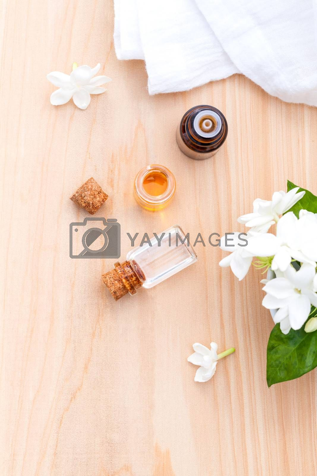 Royalty free image of Aroma oil bottles arranged with jasmine flowers on wooden backgr by kerdkanno
