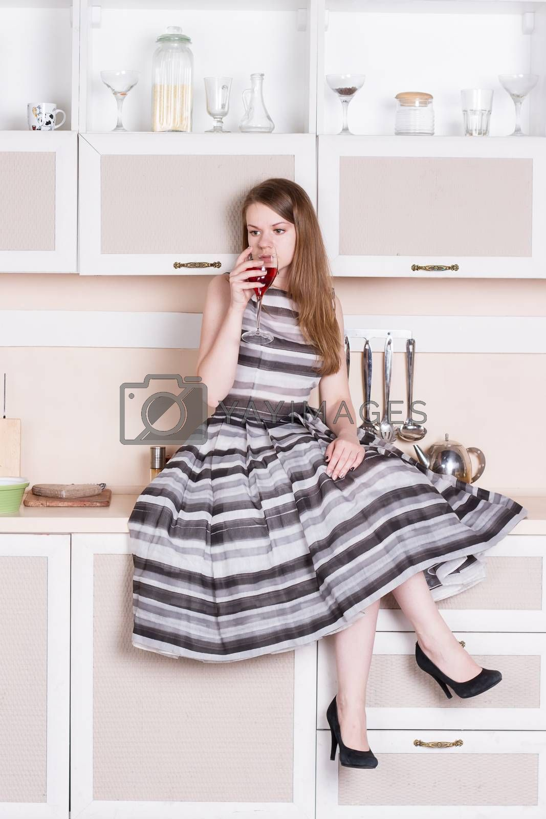 Royalty free image of Girl  lush gray dress sitting in the kitchen by victosha