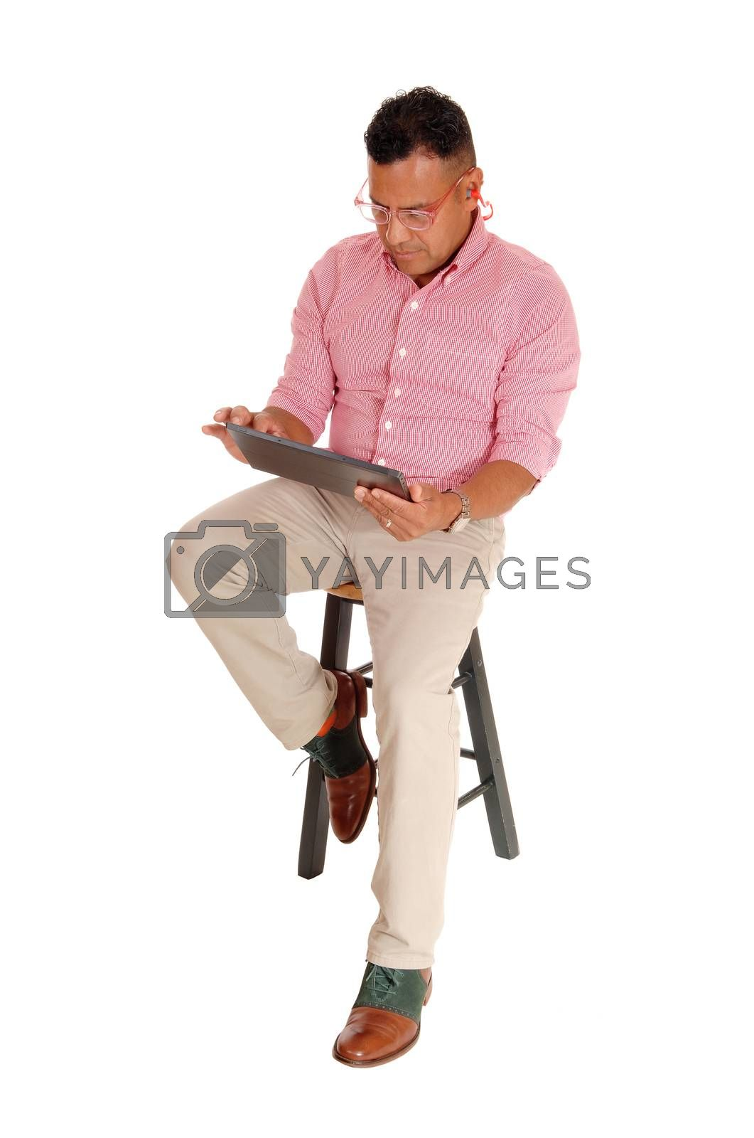 Royalty free image of Hispanic man sitting with tablet pc. by feierabend