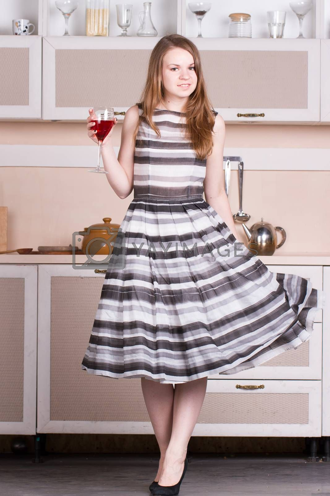 Royalty free image of Attractive young woman dress holding a glass of wine in her kitchen. by victosha