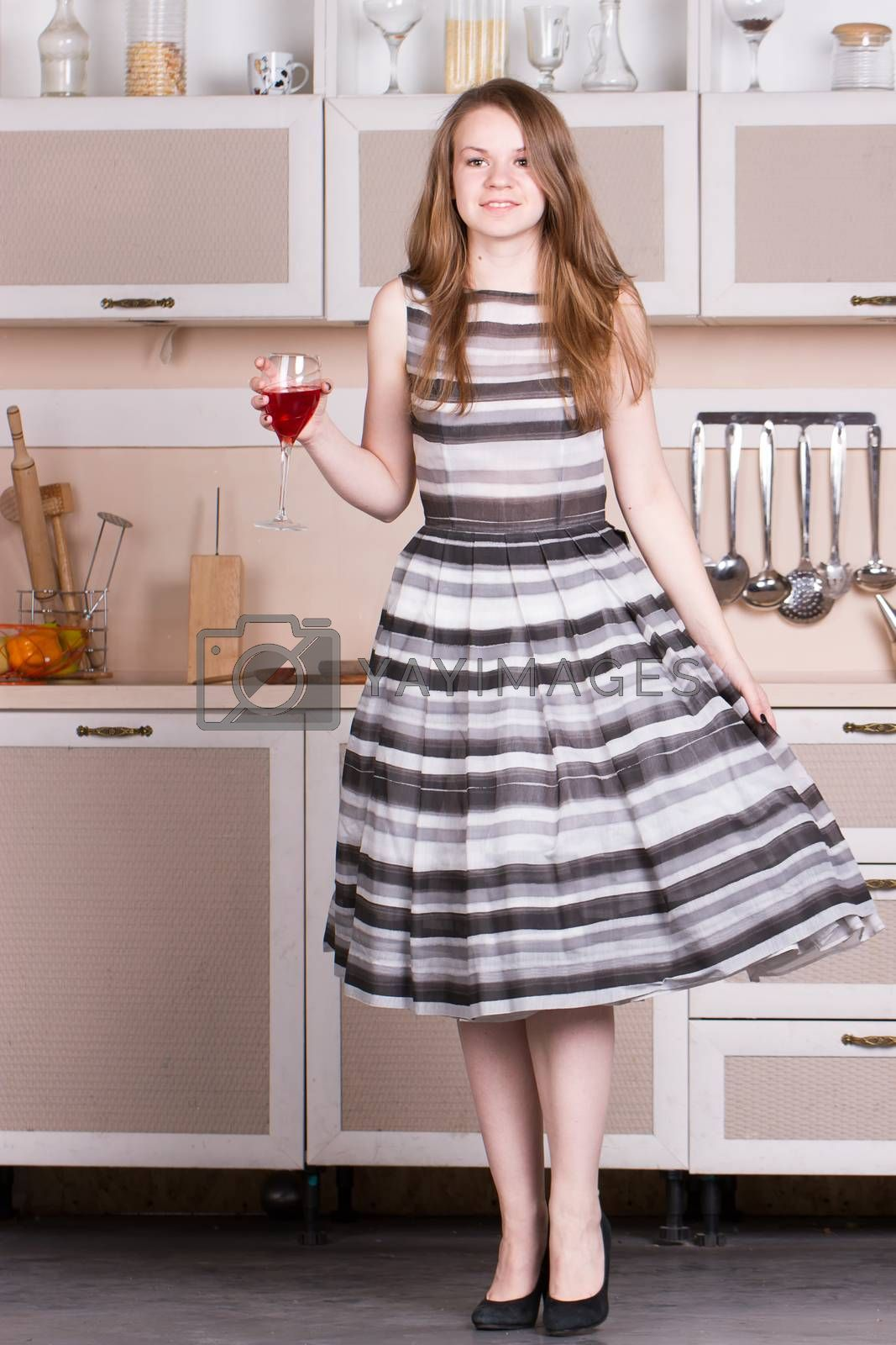 Attractive young woman dress holding a glass of wine in her kitchen. by victosha