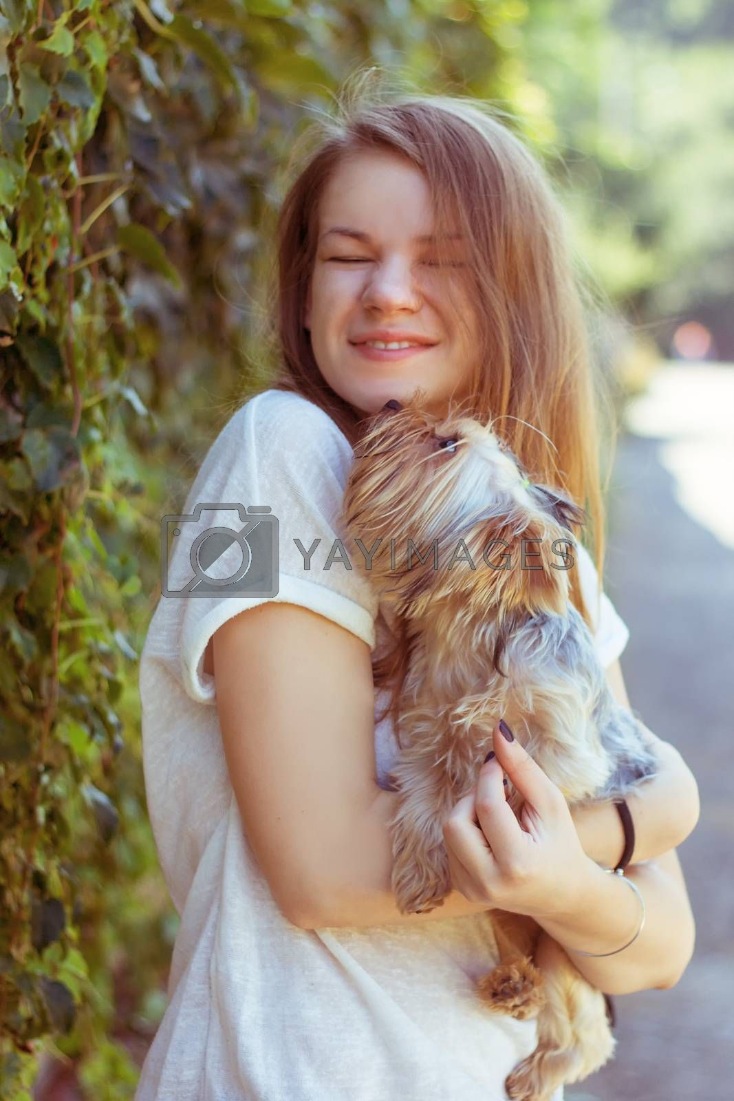 Royalty free image of Happy young girl owner with yorkshire terrier dog by victosha