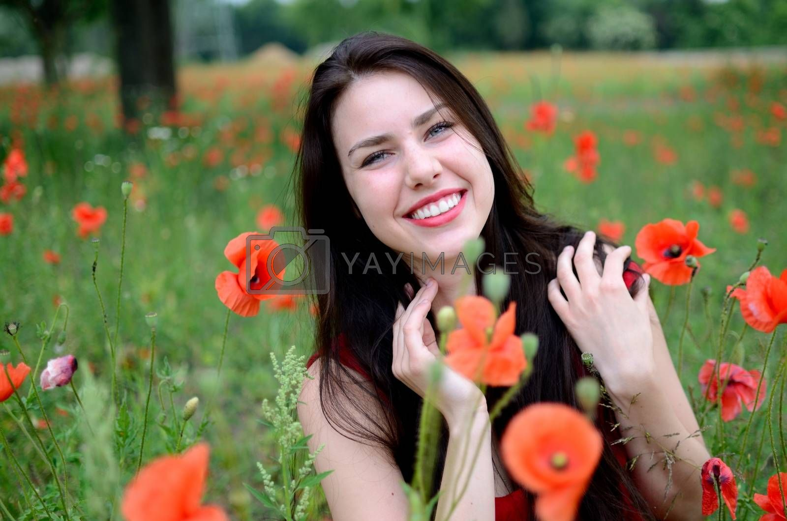 Royalty free image of Smiling girl with poppies by bartekchiny