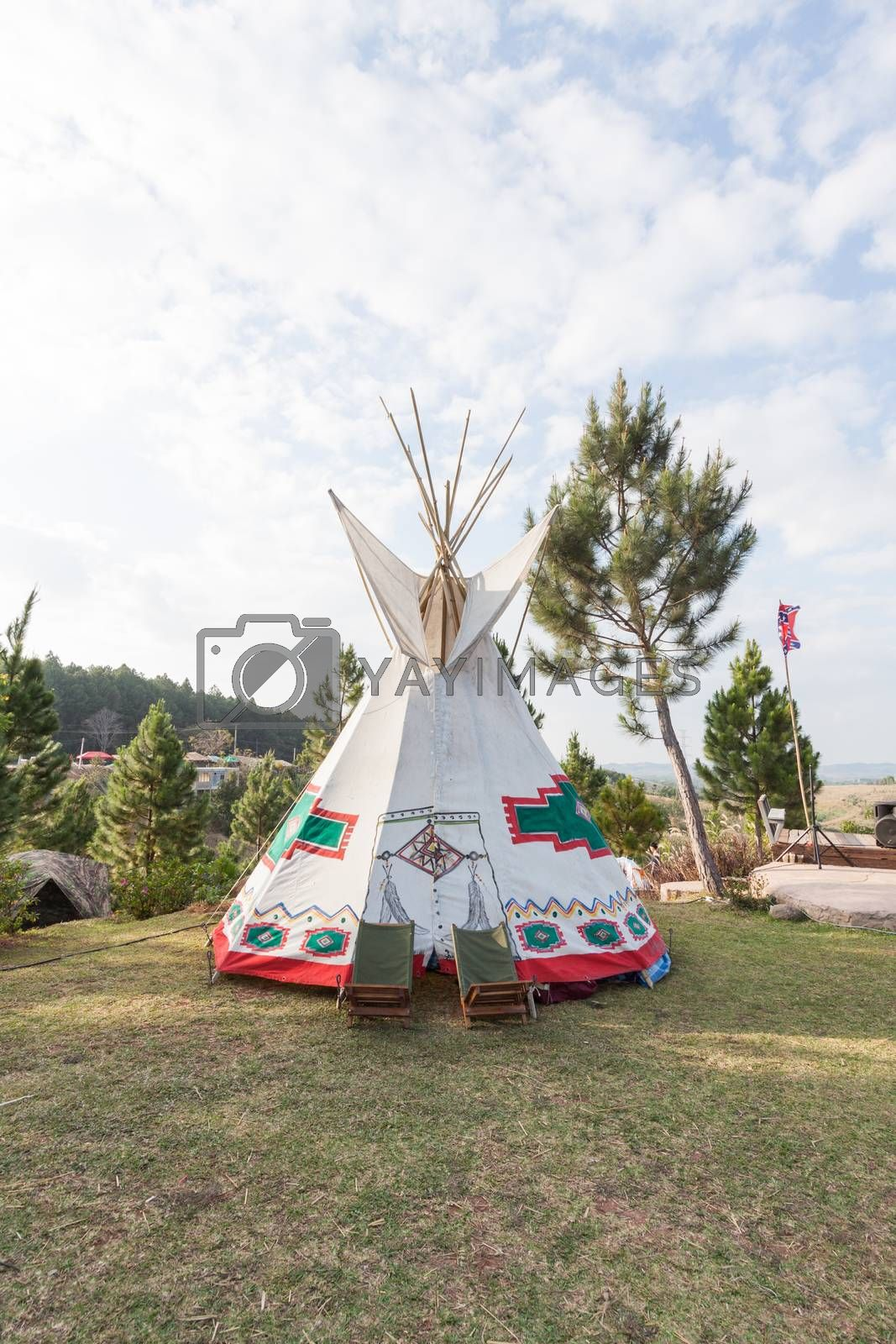 Royalty free image of An indian teepee set up in a meadow among pine wood by kritsada1992
