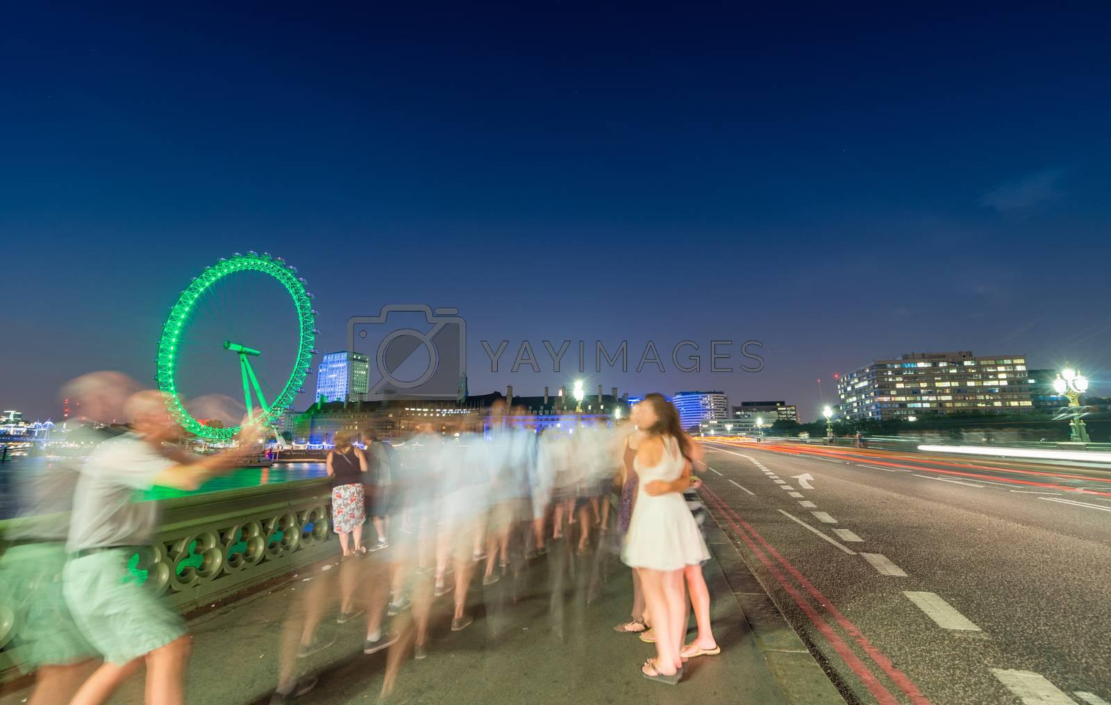 Royalty free image of Tourists enjoying Westminster Bridge at night. Blurerd moving pe by jovannig
