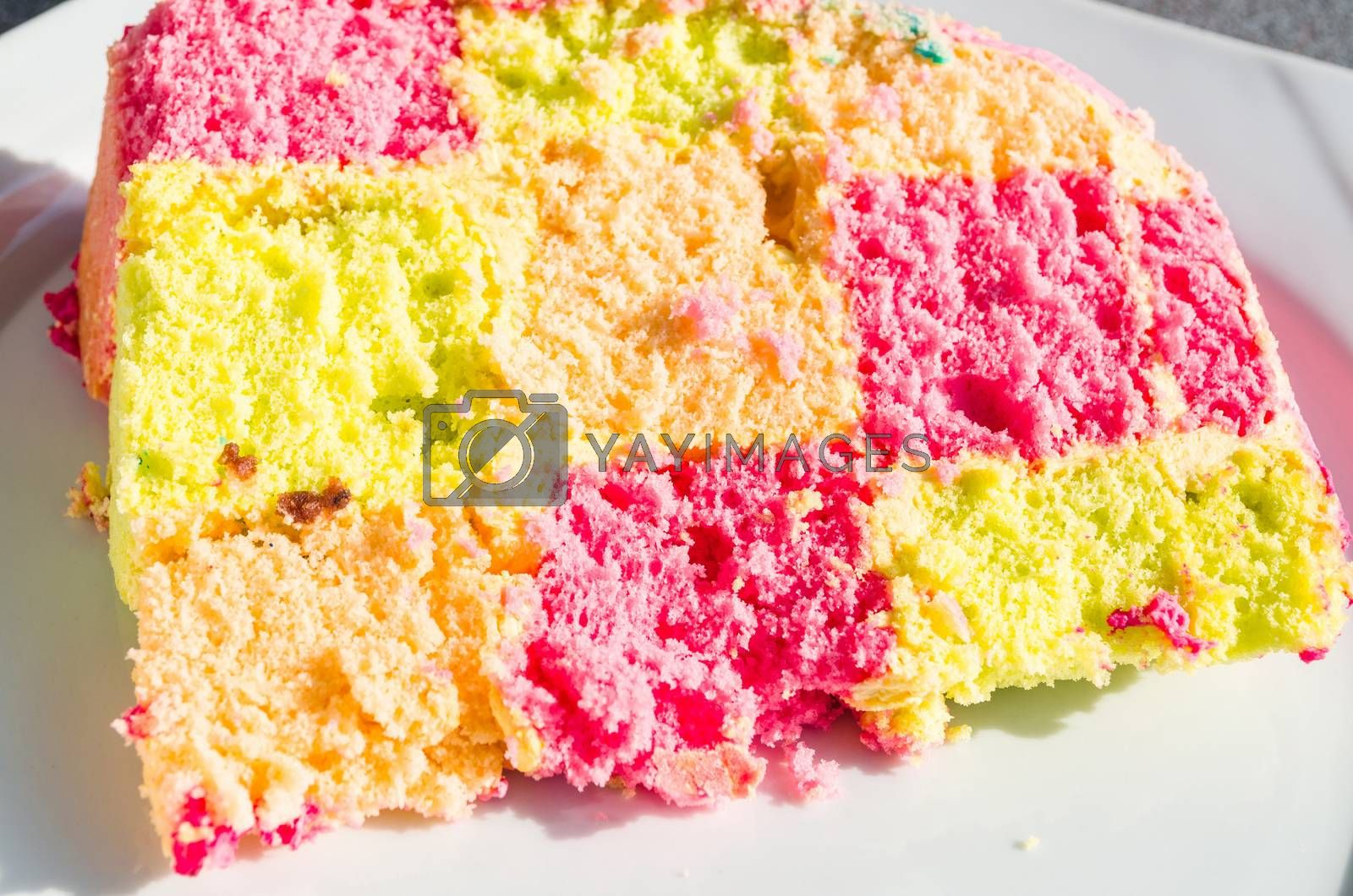 Delicious colorful checkered birthday cake. Cake on white plate.