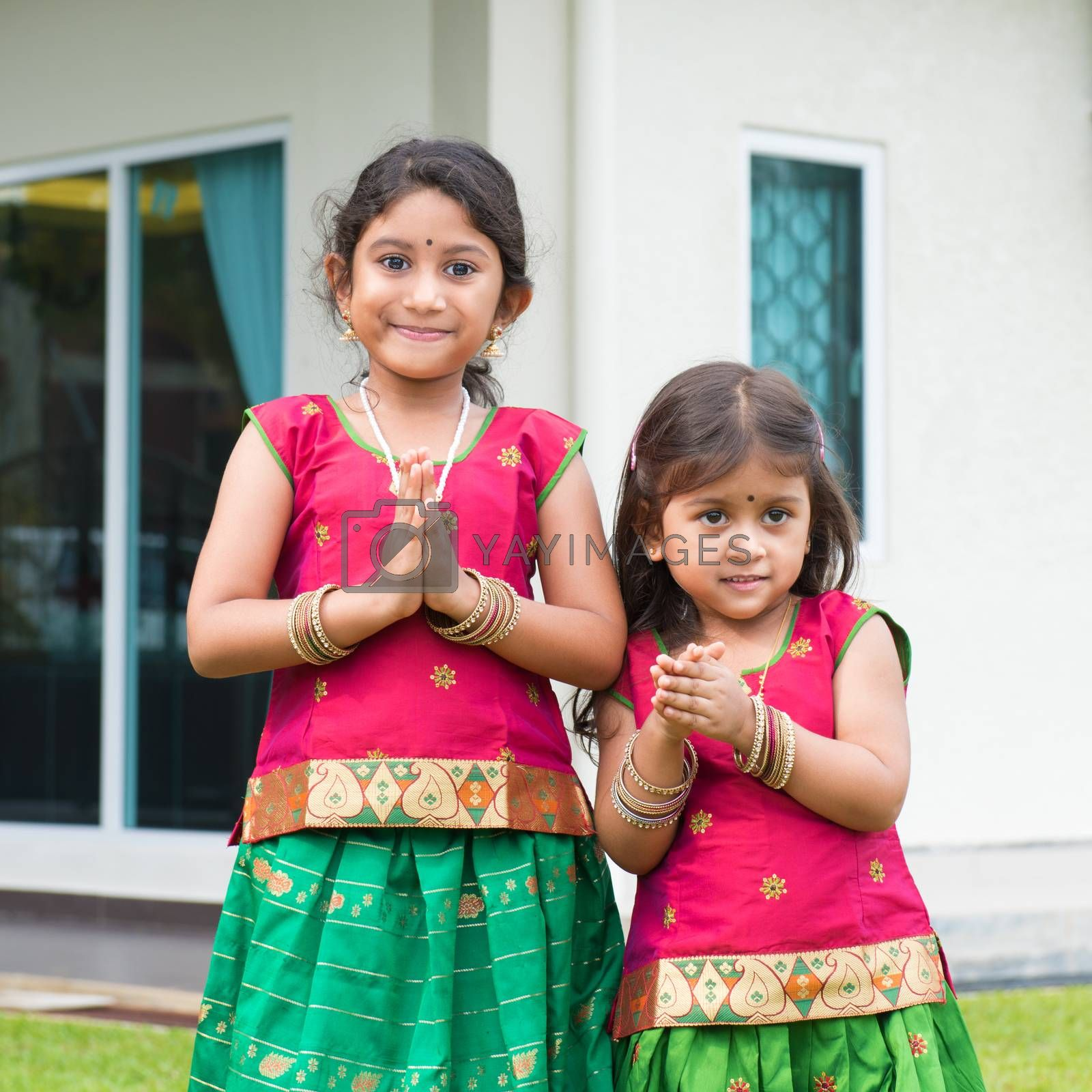 Cute Indian girls dressed in sari with folded hands representing traditional Indian greeting, standing outside their new house celebrating diwali, festival of lights.