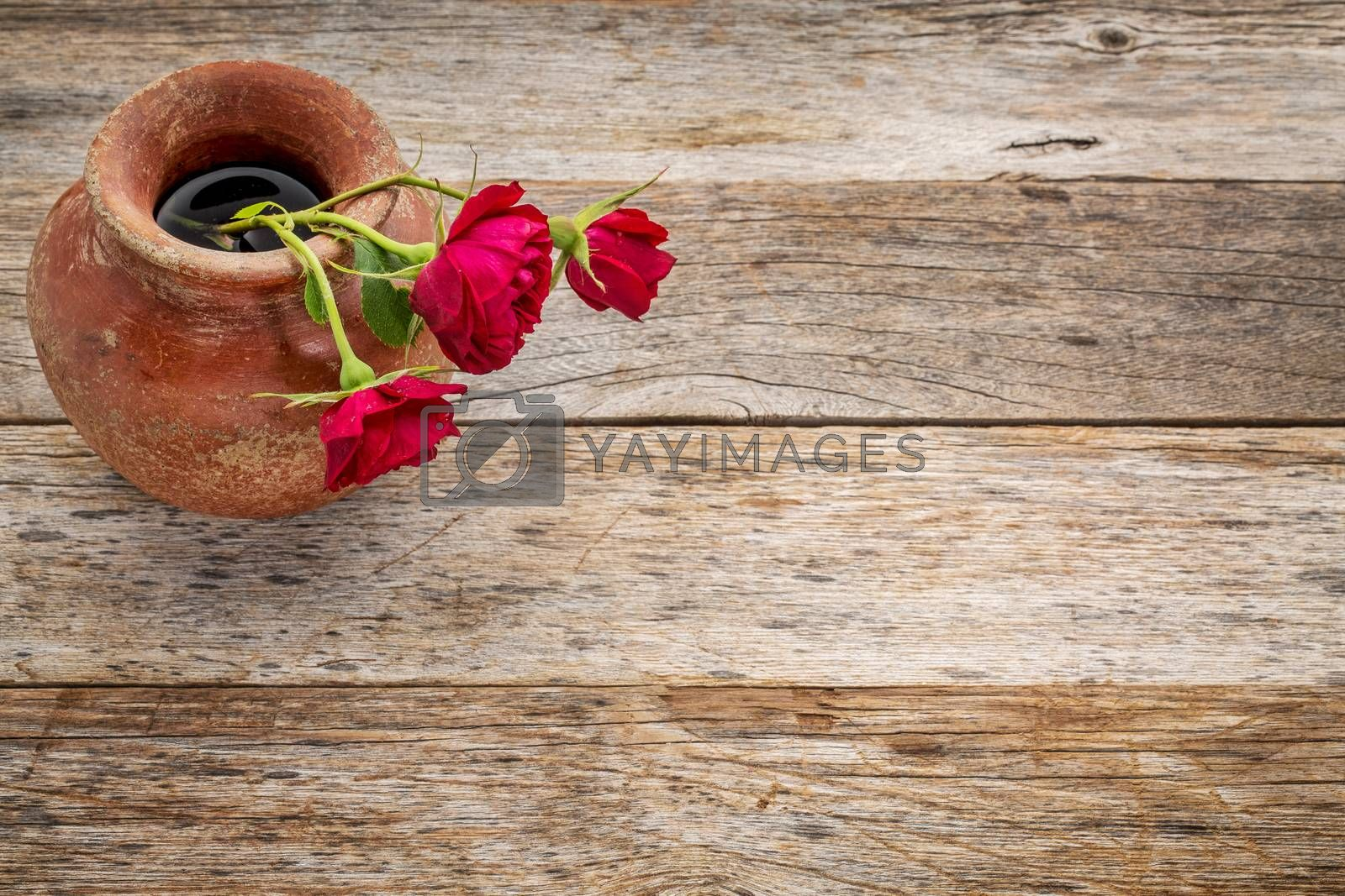 red roses in a a clay vase against rustic weathered wood with a copy space