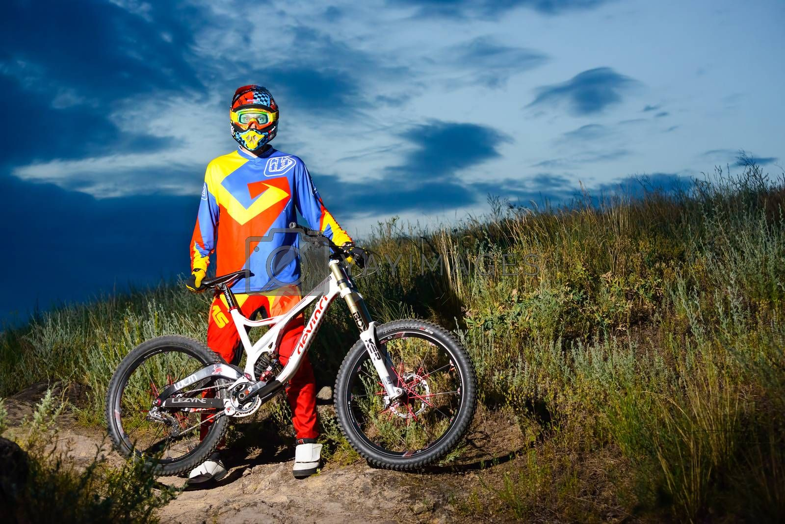 Fully Equipped Professional Downhill Cyclist with Bike on the Night Rocky Trail by maxpro