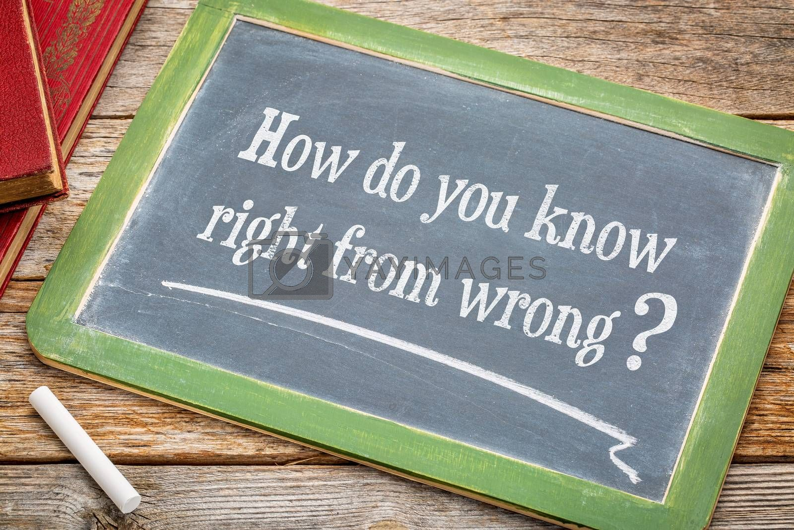 How do you know right from good - ethics question on a slate blackboard with a white chalk and a stack of books against rustic wooden table