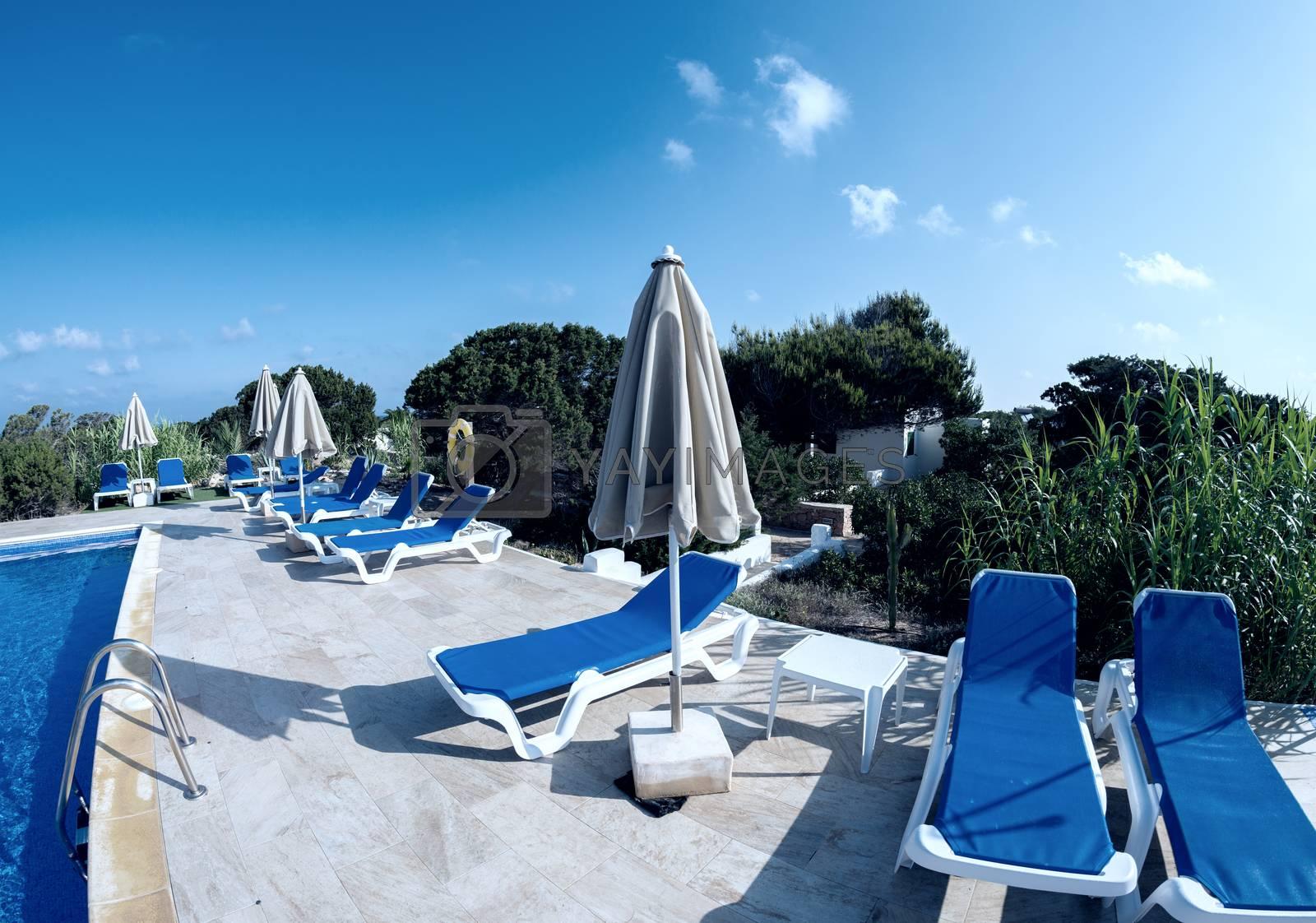 Empty sunbeds along a beautiful pool.