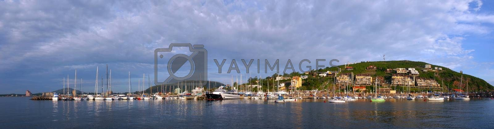 Summer coast panorama with boats in pier and cloudy skyline hill view of Piriapolis, Uruguay from the sea.
