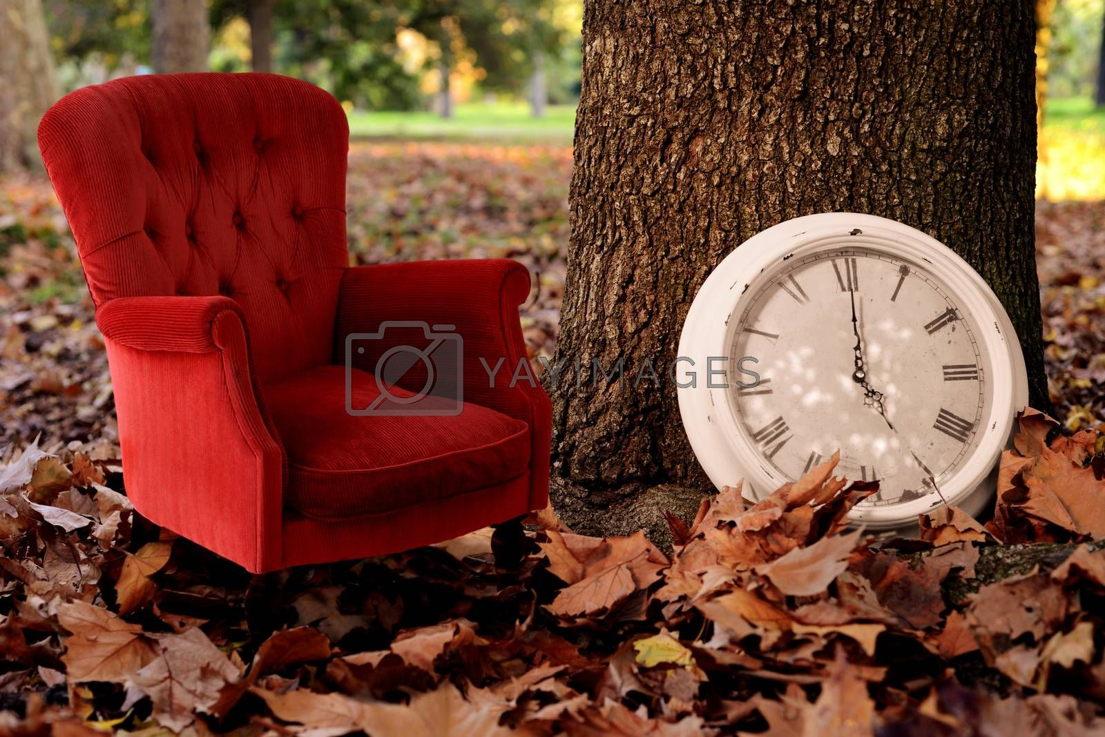 Relax is Fall time concept vintage background. Tell a autumn history creative idea photography with tree, clock and red sofa on season leaves park background.