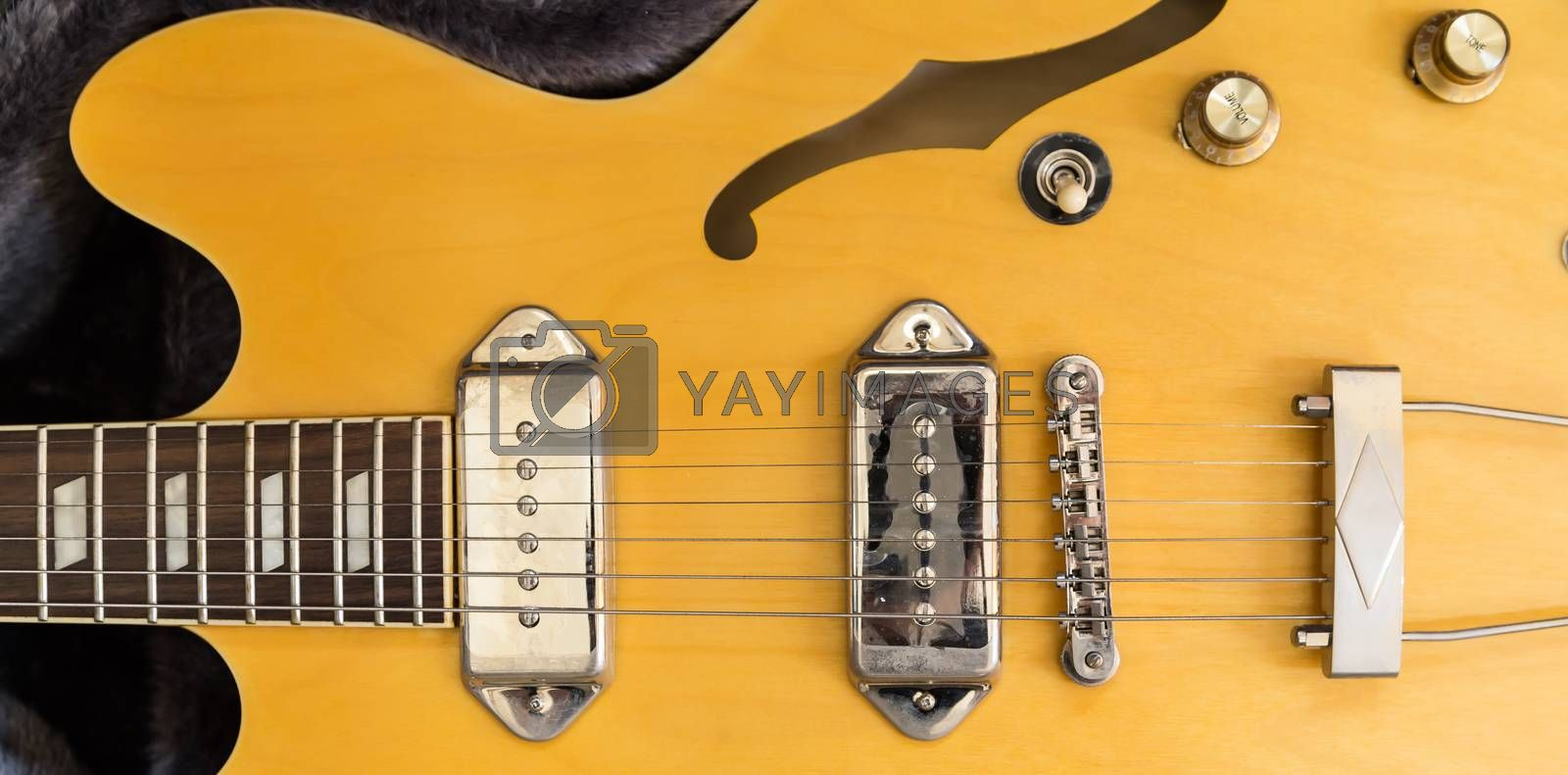 It's a part of body of a yellow electric guitar which made from wood and metal. There are 6-sling component which fix with the bar and it has a hold beside.