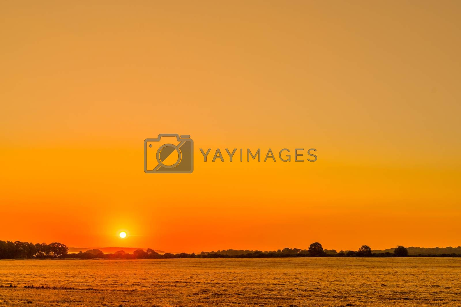 Countryside landscape with a beautiful sunrise in orange colors
