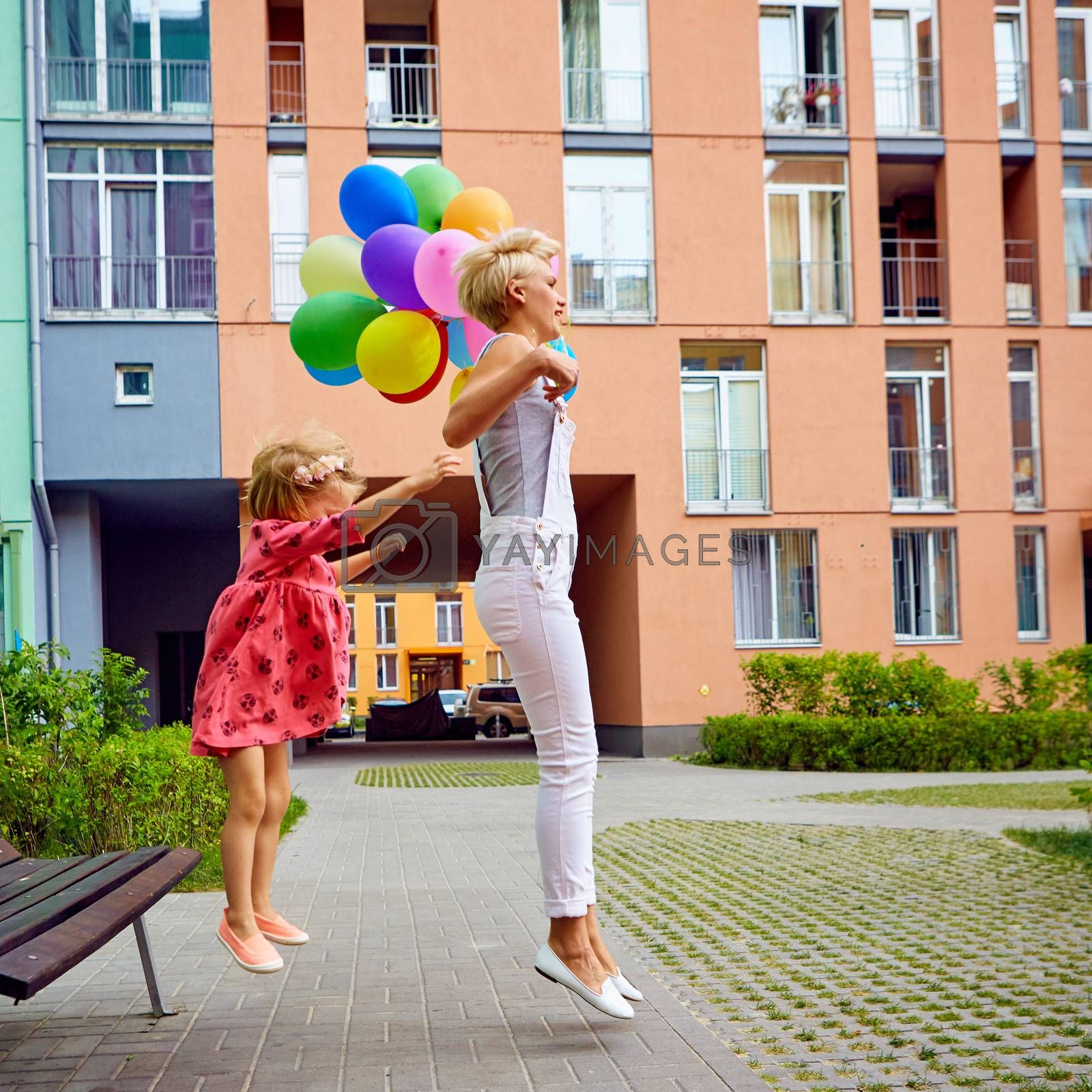 summer holidays, celebration, family, children and people concept - mother and child with colorful balloons, jumping