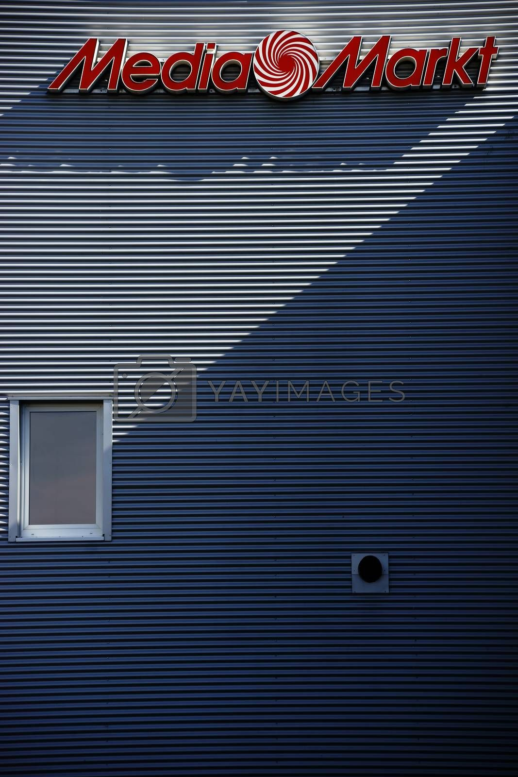 Mainz, Germany - August 28, 2015: The signboard of the electronics and HIFI market Media Markt on a modern corrugated iron facade that casts a shadow on August 28, 2015 in Mainz.