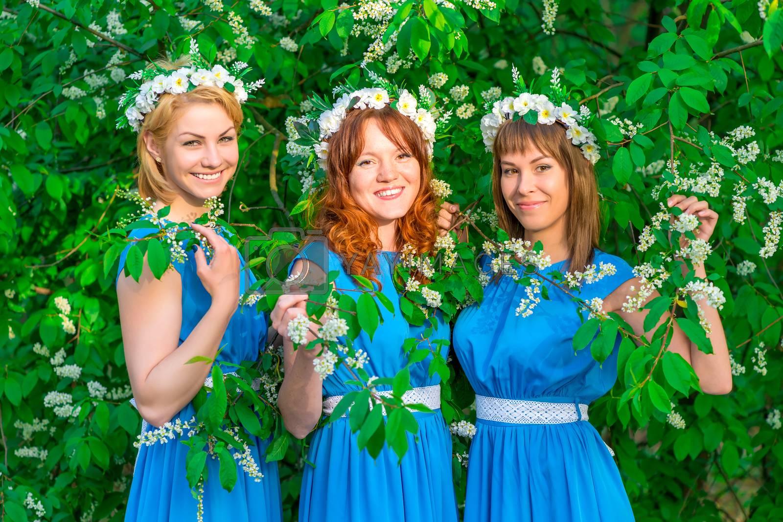 Three happy girls in identical dresses posing in the garden in spring
