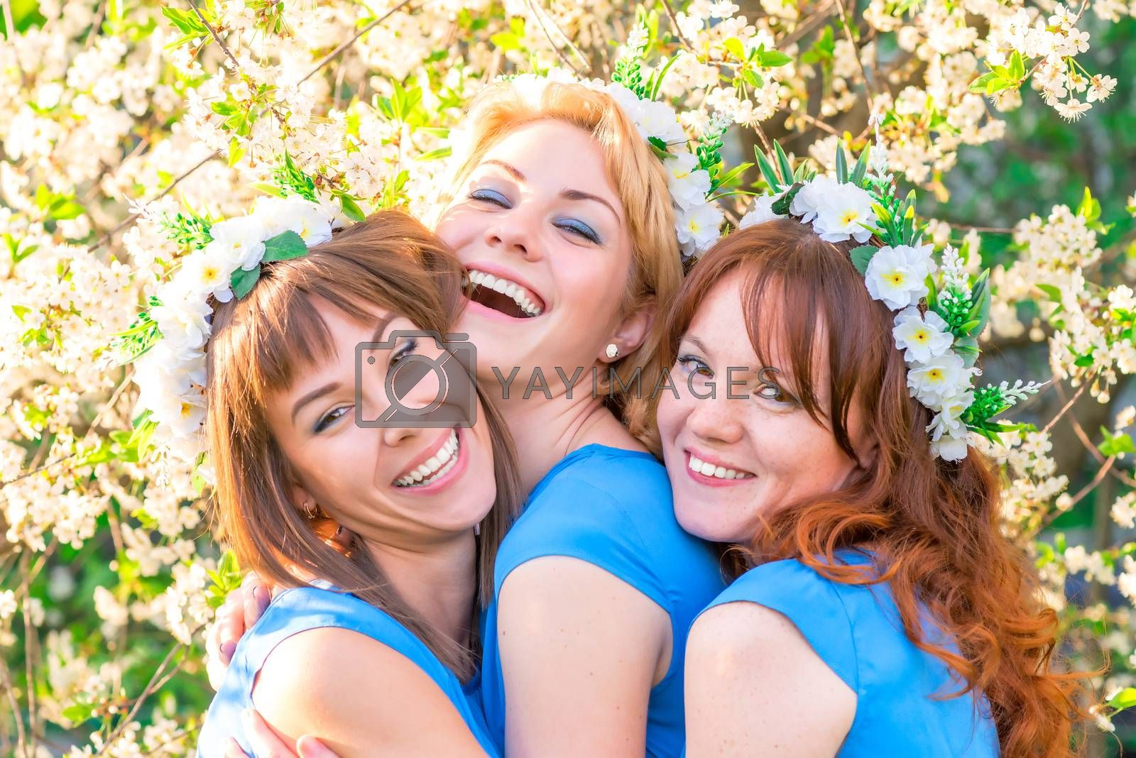 Three laughing girls in blue dresses in the lush spring garden