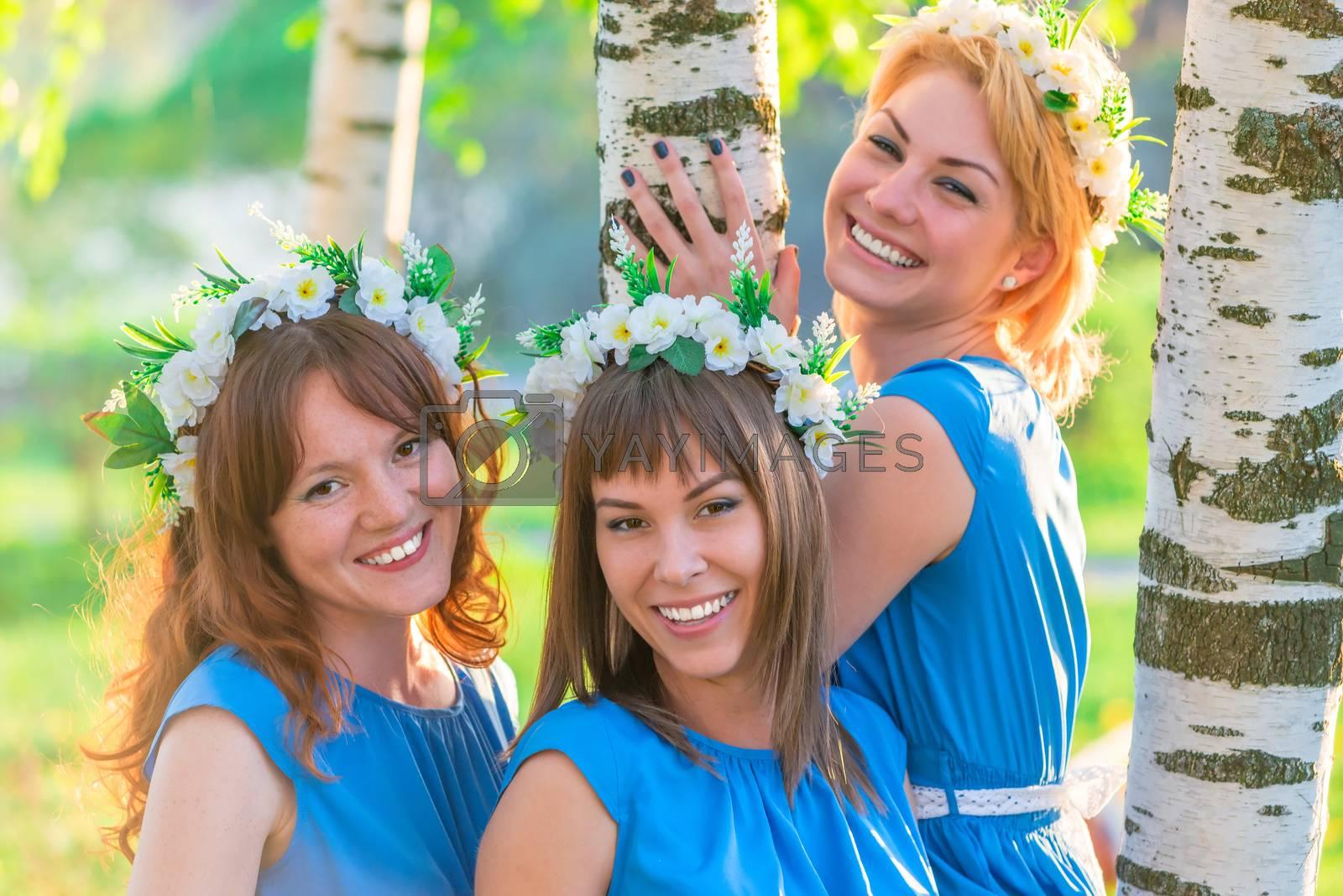 happy girlfriends posing near birch in the spring park
