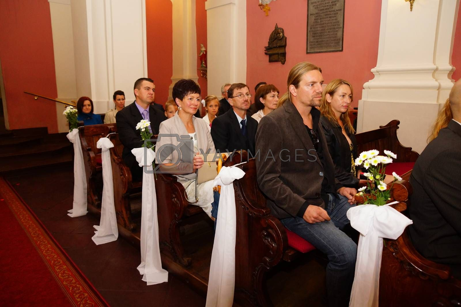 POZNAN, POLAND - SEPTEMBER 22, 2012: People sitting on benches at a church