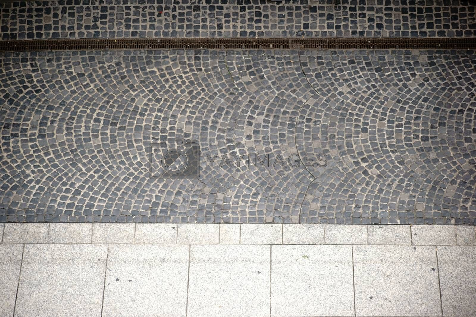 The Aerial view of a sidewalk with cobblestones and a gully.