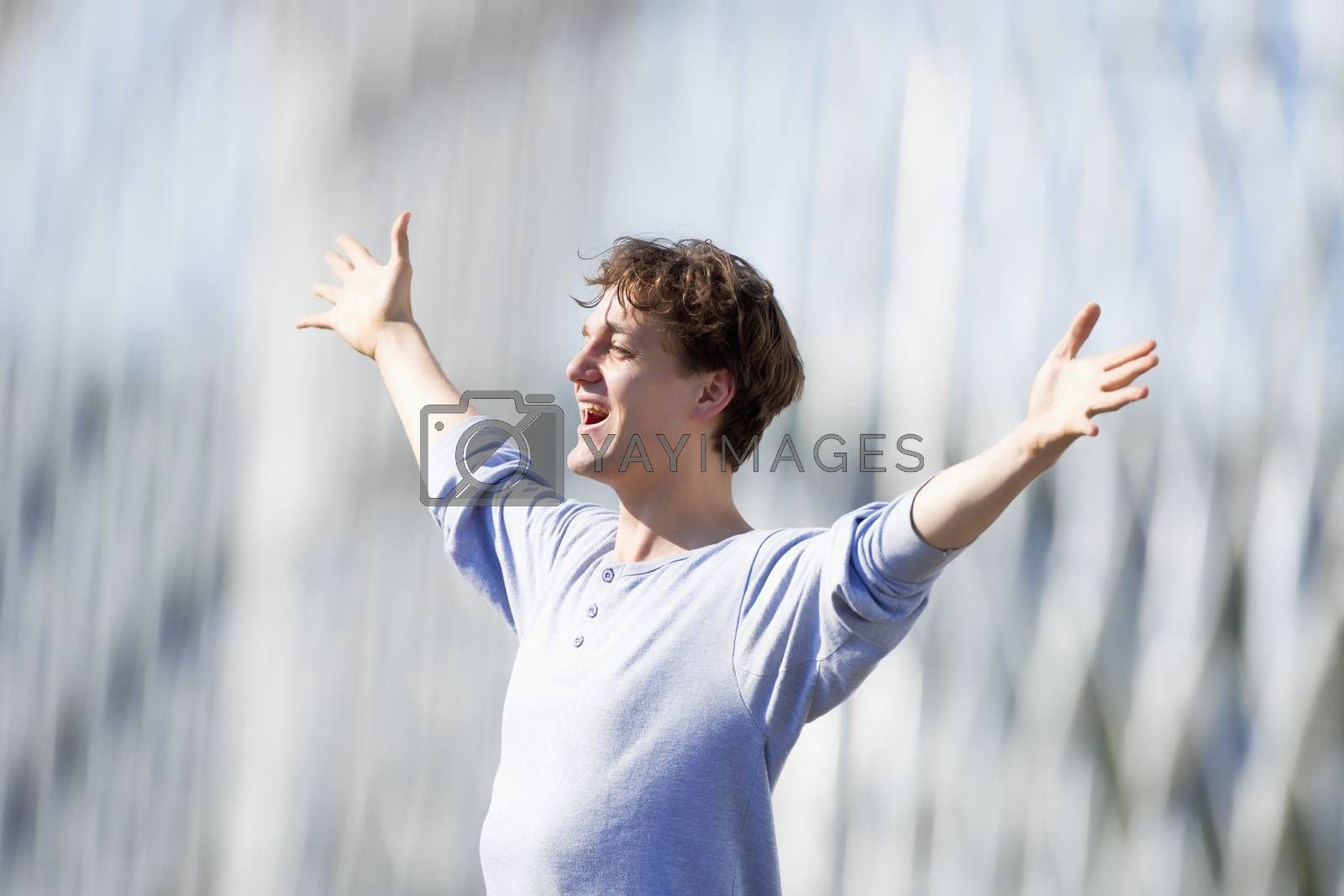 Royalty free image of Excited Young Man Stretching out his Arm in Emotion  by courtyardpix