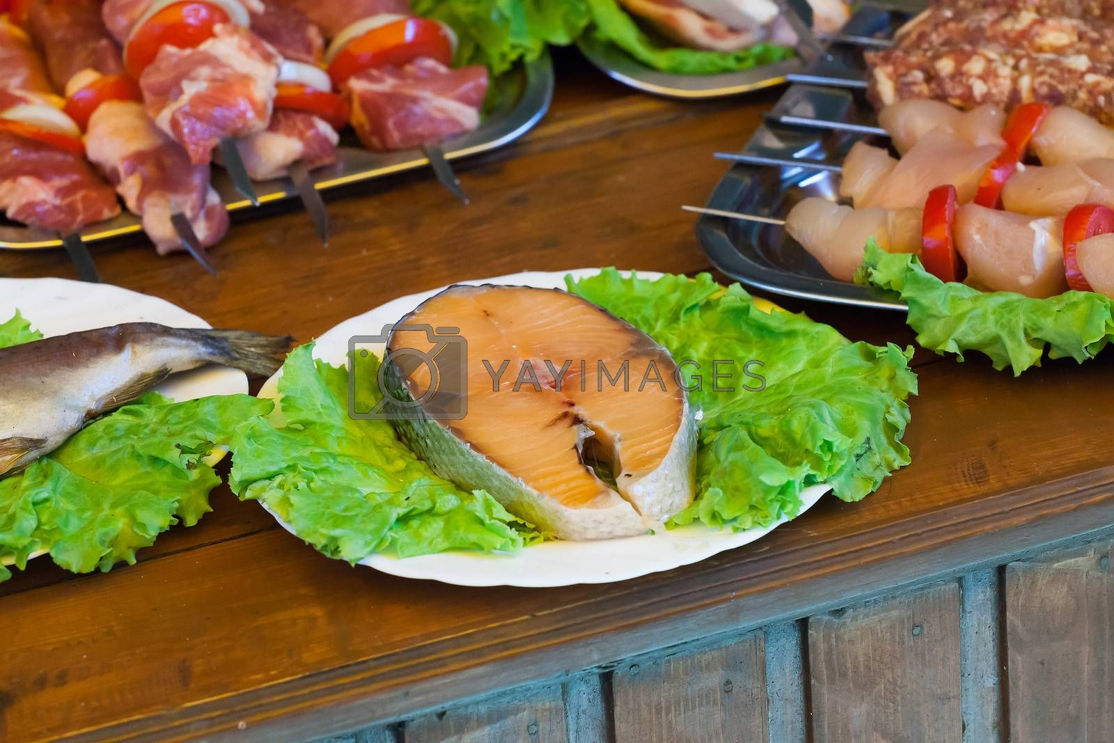 stake of a salmon on a white plate with greens on a wooden table