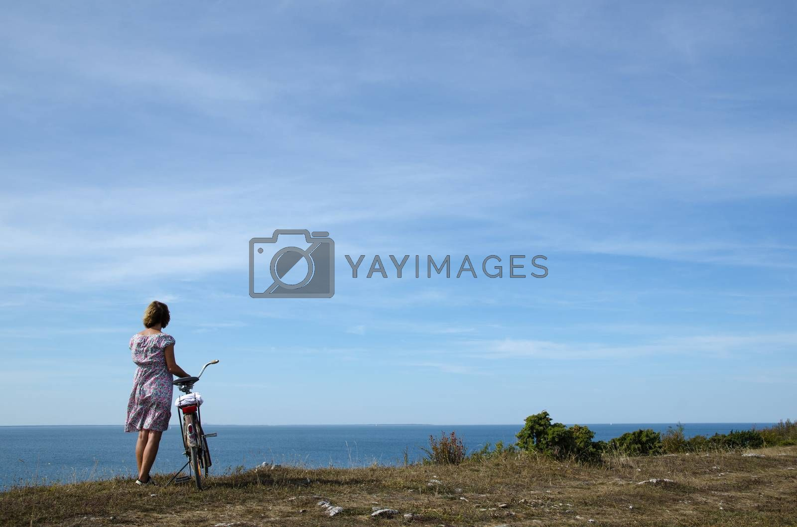 Royalty free image of Woman with bike watching view by olandsfokus