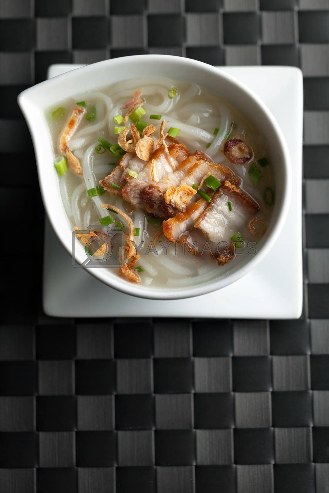 Close up top down view of Thai style crispy pork rice noodle soup in a bowl with copy space.