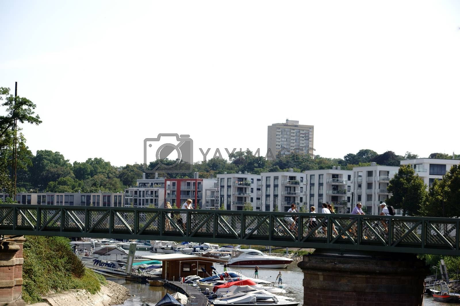 Mainz, Germany - August 22, 2015: Pedestrians and cyclists cross a bridge on the Victor Hugo banks with a river port and motorboats on August 22, 2015 in Mainz.