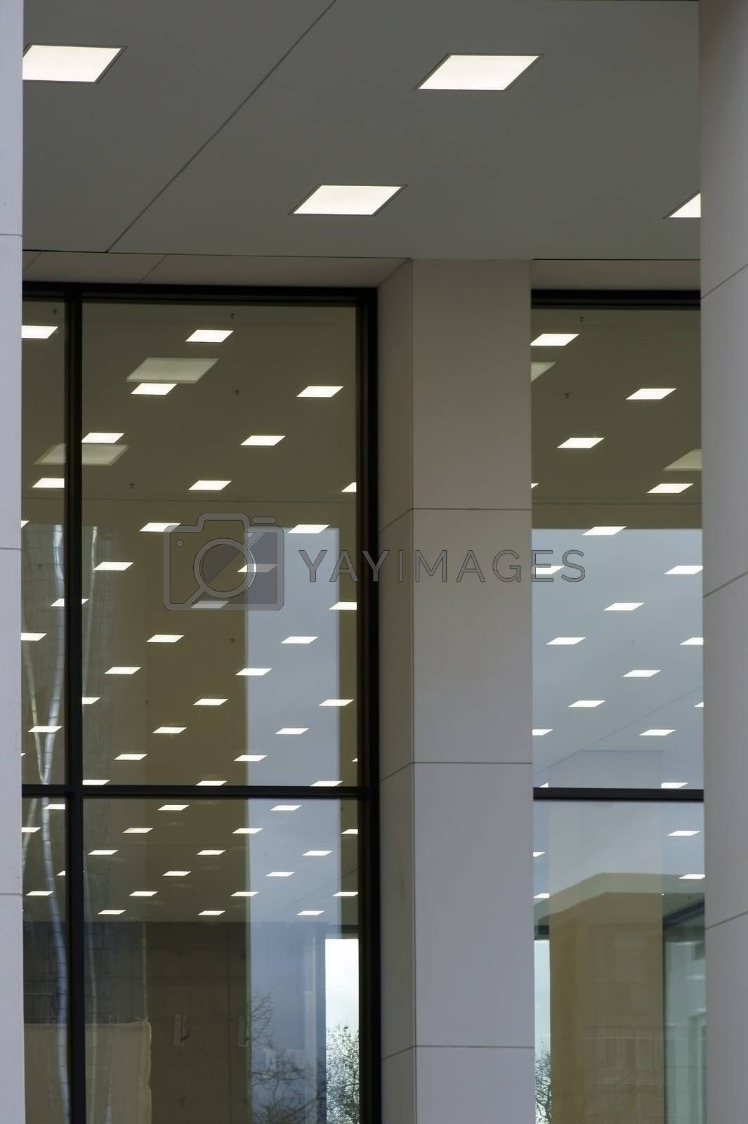 Abstract square ceiling lights are reflected in the glass windows of a panoramic window or storefront.