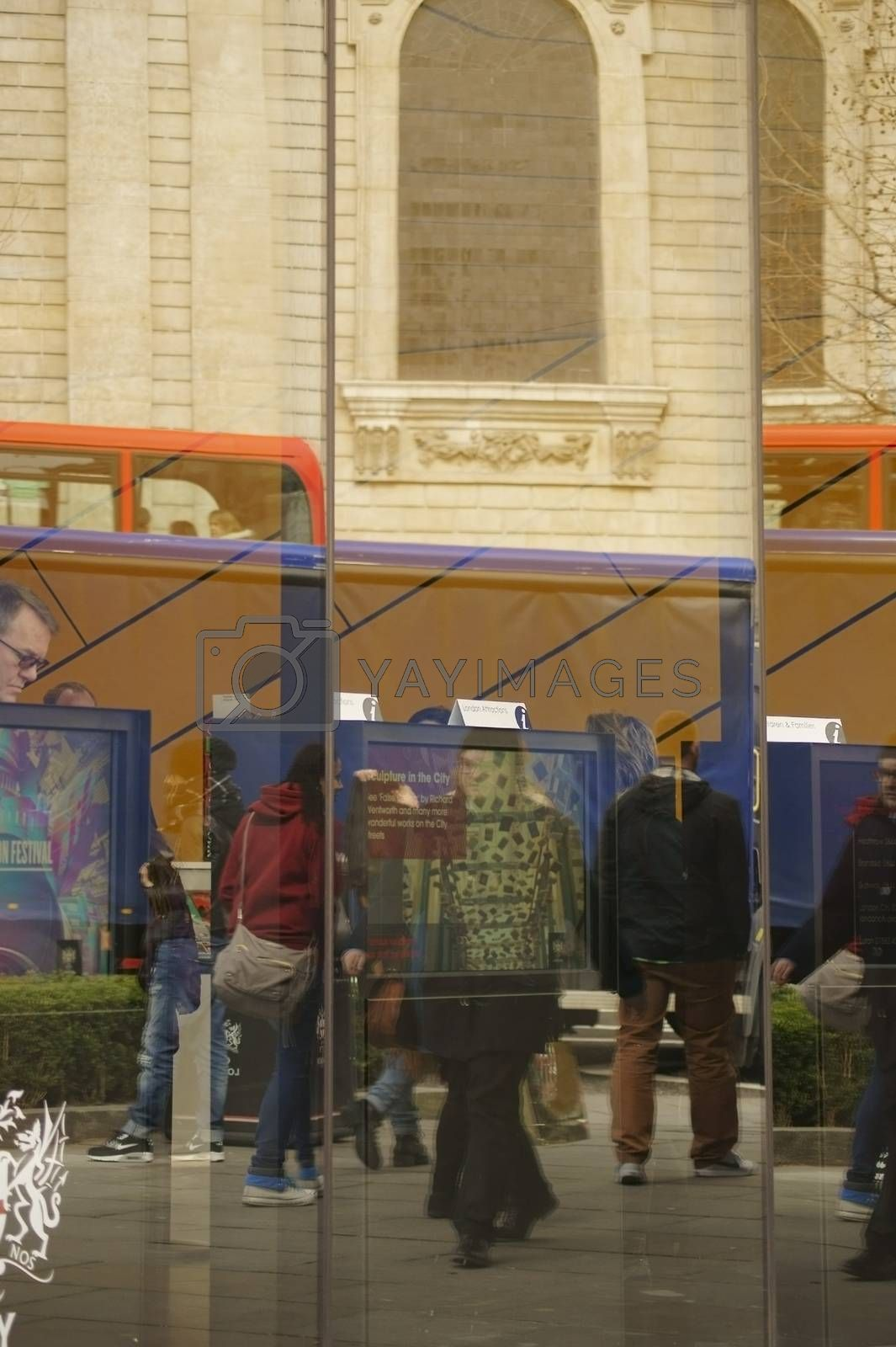 London, UK - April 01, 2015: The Reflections of tourists and red double-decker buses in the windows of an information center at the St. Paul's Cathedral on April 01, 2015 in London.