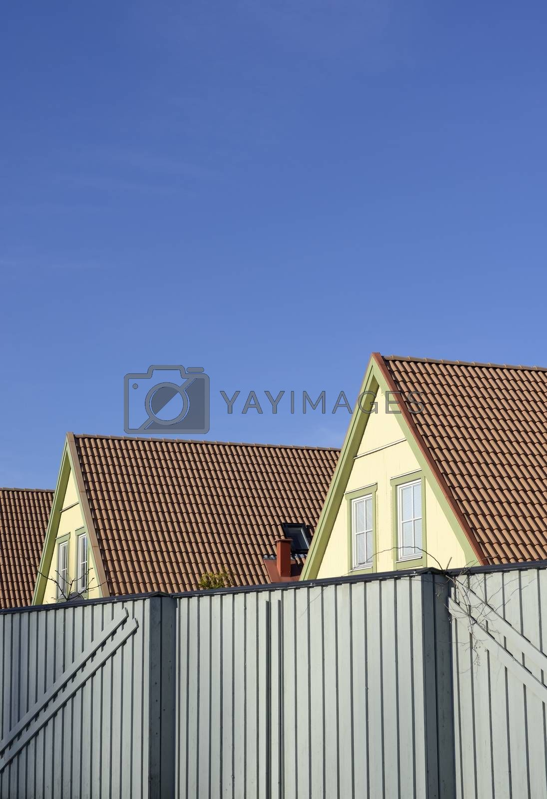 Photograph of a new house rooftop against a clear blue sky.