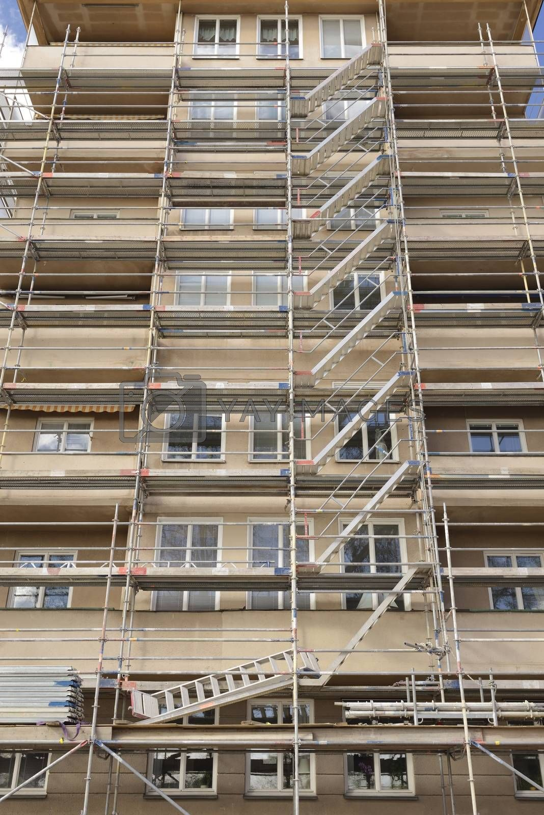 Thermal insulation being installed with scaffolding around the building