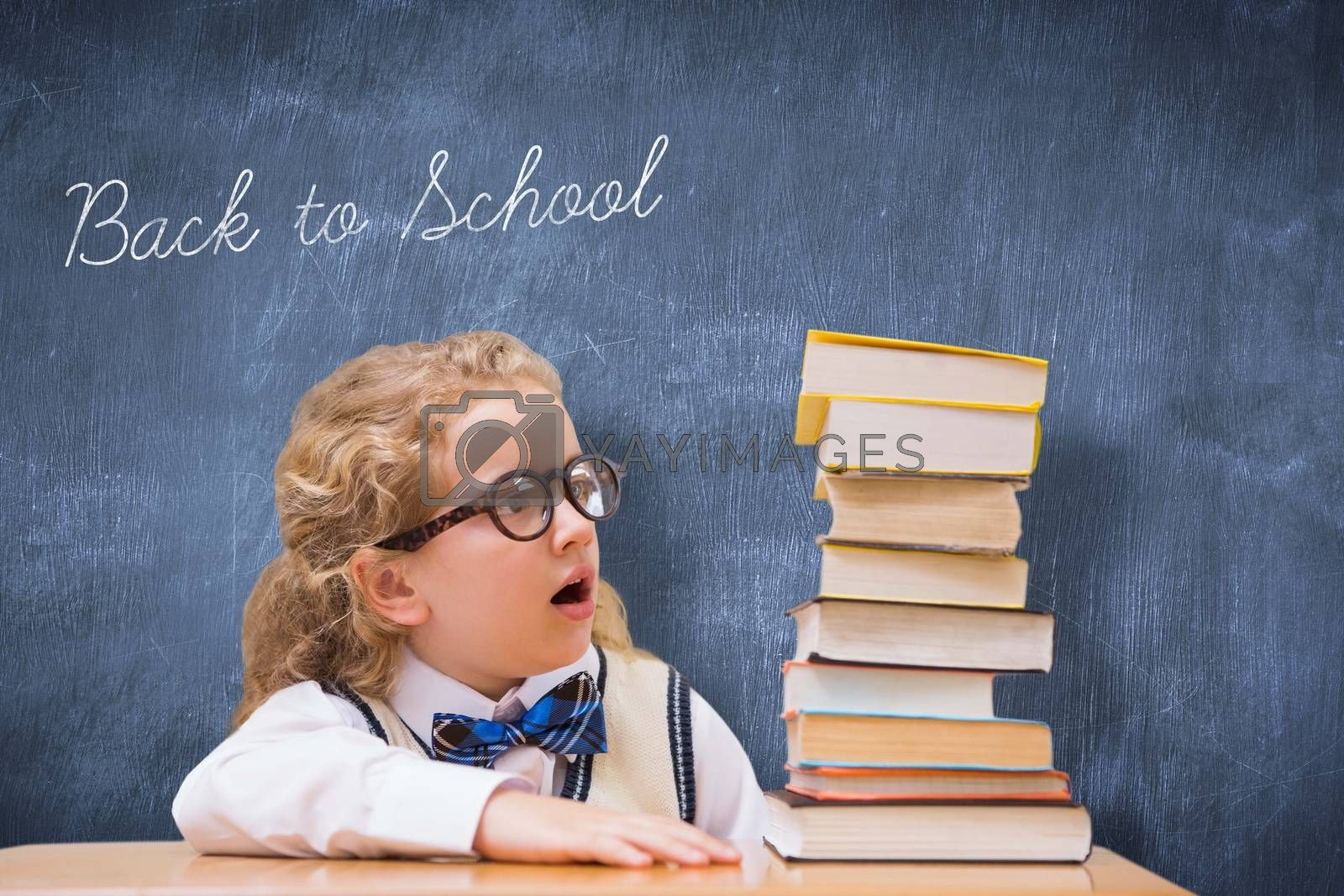 The word back to school and surprise pupil looking at books against blue chalkboard
