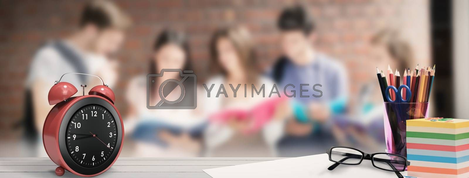 School supplies on desk against happy students standing and reading
