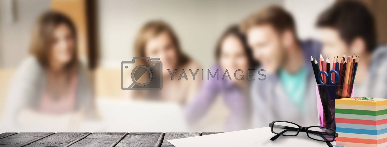 School supplies on desk against smiling friends students using laptop