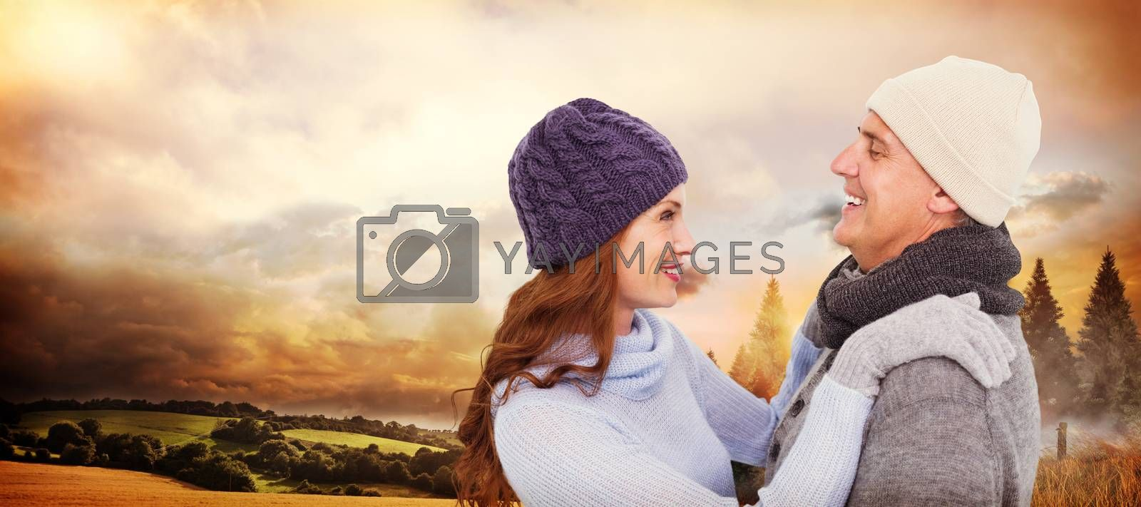 Happy couple in warm clothing against country scene