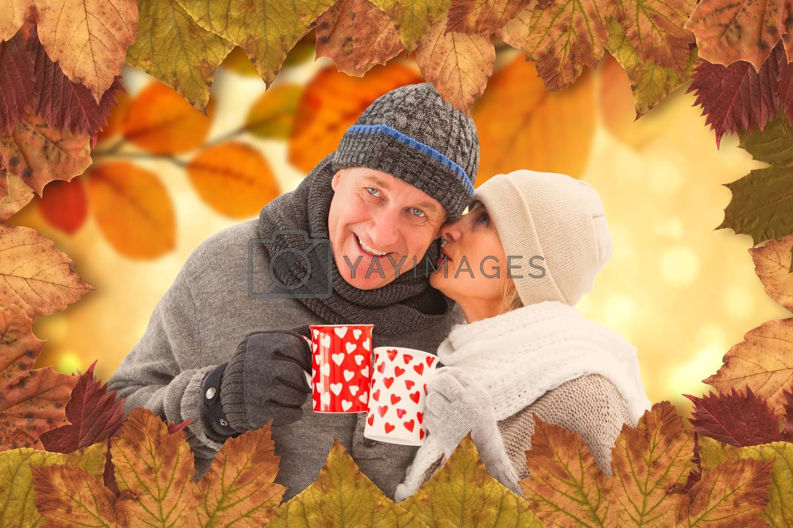 Composite image of happy mature couple in winter clothes holding mugs by Wavebreakmedia