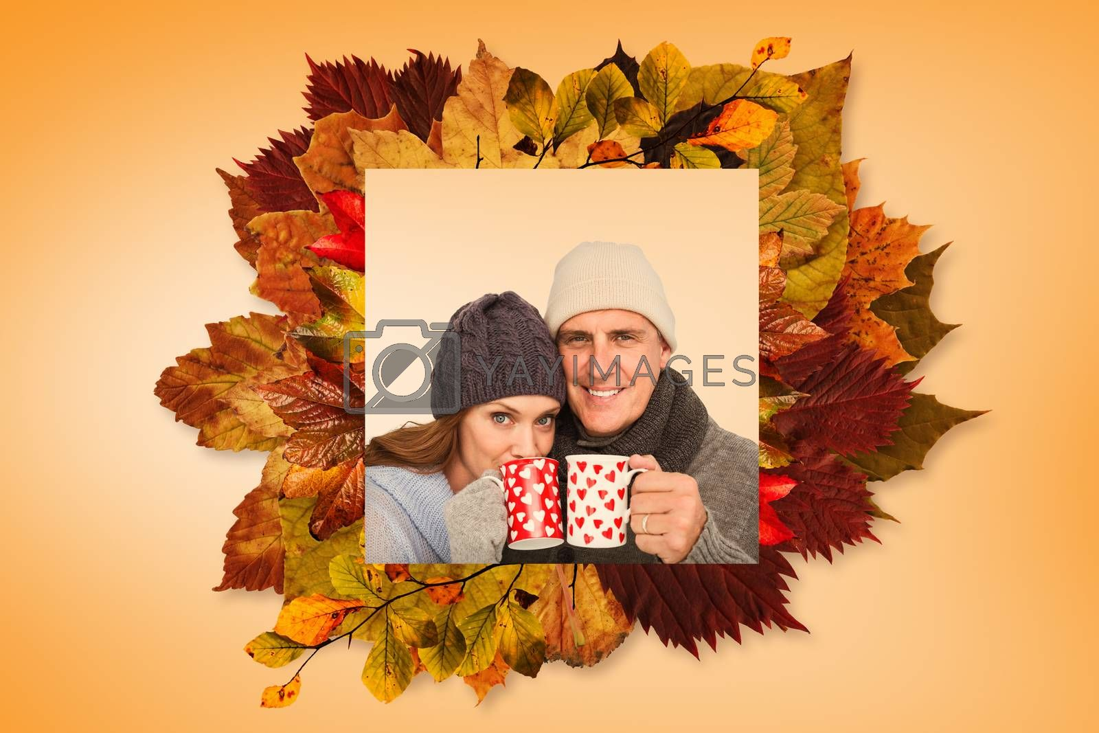 Happy couple in warm clothing holding mugs against autumn leaves pattern